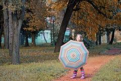 Little girl with umbrella in park autumn season Stock Photography