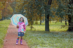 Little girl with umbrella in park autumn season Royalty Free Stock Image