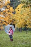 Little girl with umbrella in park autumn season Stock Image