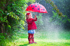 Little girl with umbrella playing in the rain. Little girl with red umbrella playing in the rain. Kids play outdoors by rainy weather in fall. Autumn outdoor fun Stock Image