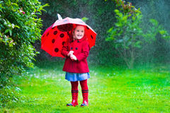 Little girl with umbrella playing in the rain. Little girl with red umbrella playing in the rain. Kids play outdoors by rainy weather in fall. Autumn outdoor fun Royalty Free Stock Photo