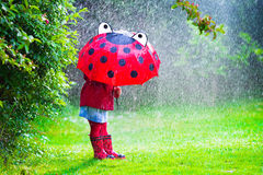 Little girl with umbrella playing in the rain. Little girl with red umbrella playing in the rain. Kids play outdoors by rainy weather in fall. Autumn outdoor fun Royalty Free Stock Image
