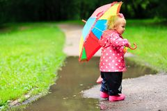 Little girl with umbrella in raincoat and boots Royalty Free Stock Image