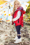 Little girl with umbrella in red vest outdoor Royalty Free Stock Images