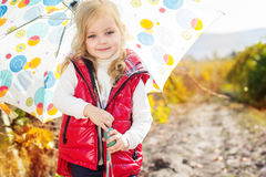 Little girl with umbrella in red vest outdoor Royalty Free Stock Image