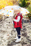 Little girl with umbrella in red vest outdoor Royalty Free Stock Photography