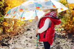 Little girl with umbrella in red vest outdoor Royalty Free Stock Photo
