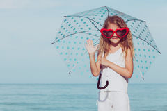 Little girl with umbrella standing on the beach at the day time. One kid having fun on the nature. Concept of happy life Stock Photos