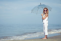 Little girl with umbrella standing on the beach at the day time. One kid having fun on the nature. Concept of happy life Royalty Free Stock Photos