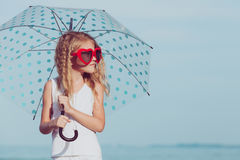 Little girl with umbrella standing on the beach at the day time. One kid having fun on the nature. Concept of happy life Stock Image