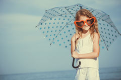 Little girl with umbrella standing on the beach at the day time. One kid having fun on the nature. Concept of happy life Stock Photography