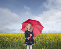 Little girl with umbrella  in front of an oilseed field Royalty Free Stock Photo