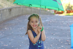 A little girl with an umbrella Stock Images