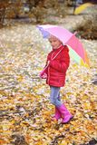 Little girl with umbrella taking walk in autumn park royalty free stock photo