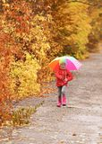 Little girl with umbrella taking walk in autumn park stock photography