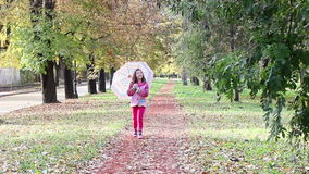 Little girl with umbrella walking in park stock footage