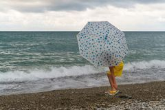 Little girl with umbrella on beach in bad weather. Little girl with an umbrella walks along beach. Curtains on sea waves and clouds. Man is unrecognizable stock images