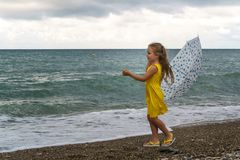 Little girl with umbrella on beach in bad weather. Little girl with an umbrella walks along beach. Curtains on sea, waves and clouds. Wind blew umbrella royalty free stock photos