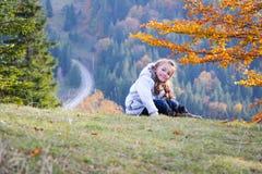 Little girl under autumn yellow tree Royalty Free Stock Image