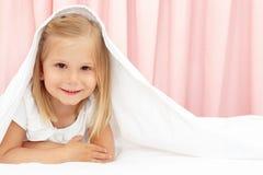 Little girl under the blanket stock photo