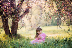 Little girl under blooming apple tree royalty free stock photo