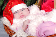Little girl under the Christmas tree on new year's cap Stock Photo