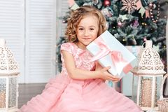 Little girl under the Christmas tree unpacking presents Royalty Free Stock Photo