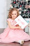 Little girl under the Christmas tree unpacking presents Stock Image
