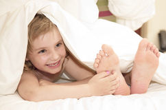 Little girl under cover Stock Images