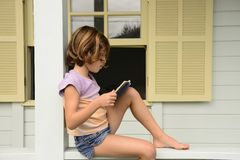 Little girl under daylight,  at home reading a book of fairy tales. Royalty Free Stock Photography