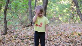Little girl under falling autumn leaves stock footage