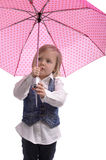 Little girl under a pink  with dots umbrella Royalty Free Stock Photo