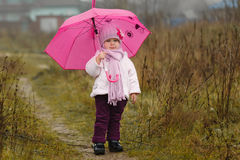 The little girl under an pink umbrella in the fall Stock Images