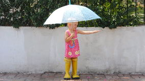 Little girl under the rain. With umbrella stock video