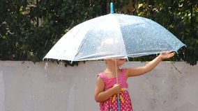 Little girl under the rain. With umbrella stock video footage