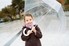 Little girl under the transparent umbrella outside, rainy day. Stock Photos