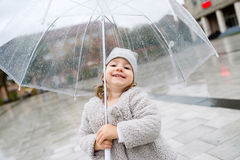 Little girl under the transparent umbrella outside, rainy day. Stock Photo
