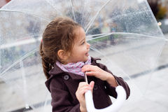 Little girl under the transparent umbrella outside, rainy day. Stock Images