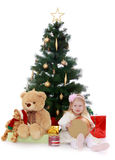 Little girl under the tree. Adorable little blonde girl sits on the floor near the Christmas tree. Girl holding a round box which is a gift. Beside her sits a Stock Photos
