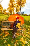 Little girl under umbrella on bench Royalty Free Stock Photos