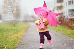 The little girl under an umbrella in the fall Stock Photos