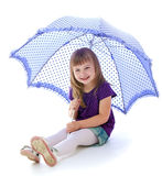 Little girl under an umbrella. Stock Image