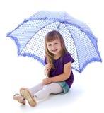 Little girl under an umbrella. stock image