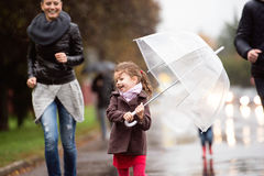 Little girl under the umbrella with her family, running. Rainy d Royalty Free Stock Photos