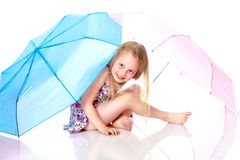 Little girl under an umbrella. A nice little girl hid under an umbrella. The concept of a happy childhood, outdoor recreation, protection from bad weather Stock Photos