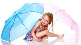 Little girl under an umbrella. A nice little girl hid under an umbrella. The concept of a happy childhood, outdoor recreation, protection from bad weather Royalty Free Stock Photography