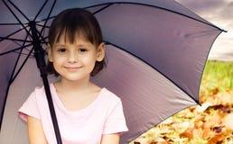Little girl under umbrella Stock Image