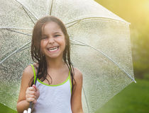 Little girl under umbrella in rainy day Stock Image