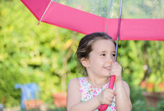 Little girl under umbrella in a rainy summer day Stock Photography