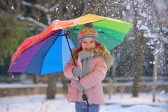 Little girl under umbrella in winter royalty free stock photography